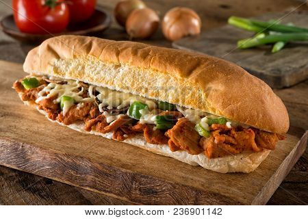 A Delicious Spicy Barbecue Pork Submarine Sandwich On A Rustic Wood Table Top.