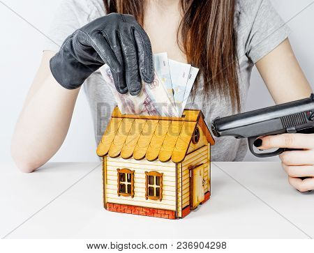 Robbery With Gun's. Gun And Money In A Hands. A Murderer Holding A Gun Attacks A Toy House Stealing