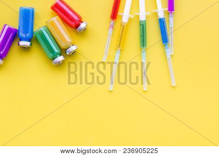 Medical Injection Syringe And Bottle With Remedy On Yellow Background Top View.