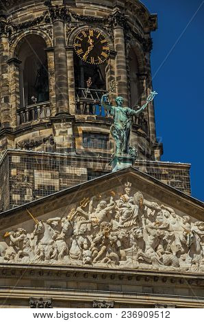 Close-up Of Facade With Sculptures And Dome With Golden Clock In The Royal Palace Of Amsterdam. The