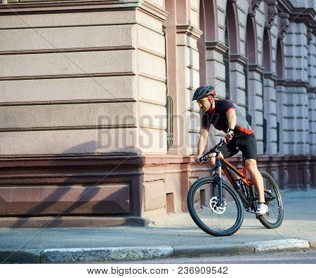 Handsome Sportsman In Professional Cycling Sportswear And Protective Helmet Riding Bicycle Along Old