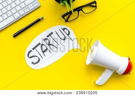 New Business, Start Up Concenpt. Megaphone Near Words Start Up In Cloud On Yellow Background Top Vie