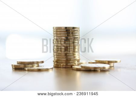 Stack Of Golden Coins On White Background With Coins Lying Around On White Background.