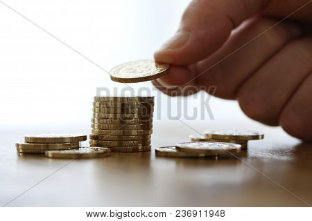 Hand Put Gold Coin To Money Stack On White Background