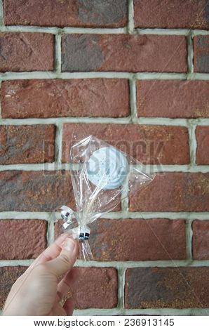 Giving Present. Meringue Lollipop In Package In Female Hand On Brick Wall Background, Copy Space