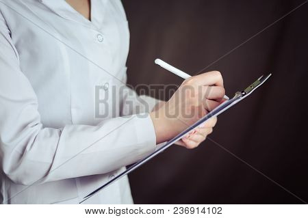 Female Doctor Hold Clipboard Pad And Fill Medical History List With Pen On Dark Background