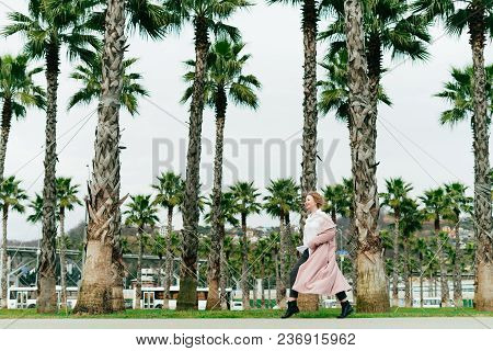Stylish Girl In A Pink Coat Walks In The Park On A Background Of Tall Green Palms, Enjoying The Long