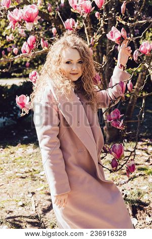 Beautiful Curly Girl In A Trendy Pink Coat Walking In The Park On A Warm Sunny Day, Smiling