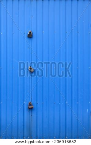 Texture Of A Metal Blue Wall With A Gate Closed For Three Locks