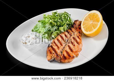 Plate With Grilled Salmon With Lemon And Greens On A Black Background. Close Up, Restaurant, Cafe, P