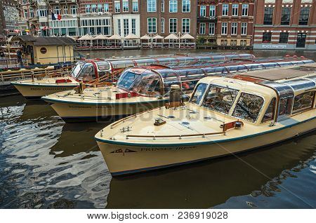 Amsterdam, Northern Netherlands - June 26, 2017. Canal With Brick Buildings And Boats Moored In Pier