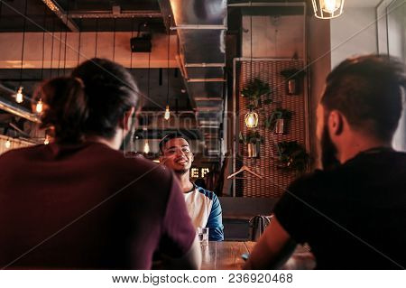 Group Of Mixed Race Young Men Talking In Lounge Bar. Multiracial Friends Having Fun In Cafe Drinking