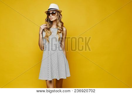 Sexy And Sensual Blonde Model Young Woman With Sexy Lips, In White Striped Dress, Hat And Sunglasses