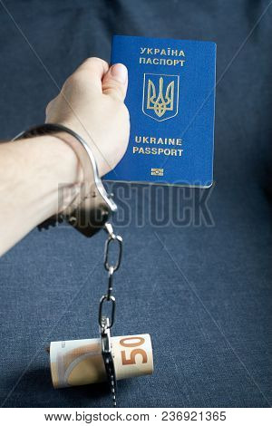 Ukrainian Biometric Passport And Handcuffs On Arm With Money On The Table