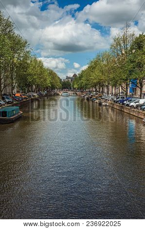 Tree-lined Canal With Old Brick Buildings, Bridge, Moored Boats And Sunny Blue Sky In Amsterdam. The