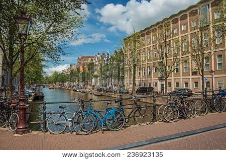 Amsterdam, Northern Netherlands - June 26, 2017. Bridge On Canal With Iron Balustrade, Bicycles, Old