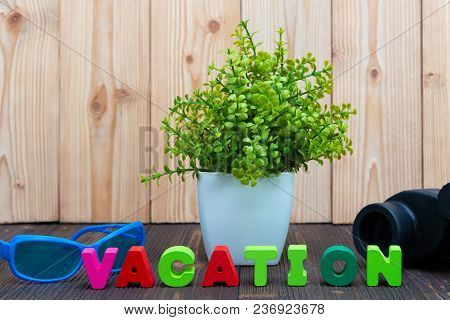 Vacation Letters Text And Notebook Paper, Alarm Clock And Little Decoration Tree In White Vase On Wo