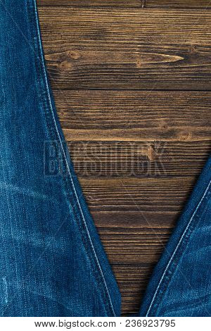 Frayed Jeans Or Blue Jeans Denim Collection On Rough Dark Wooden Table Background, Top View With Cop