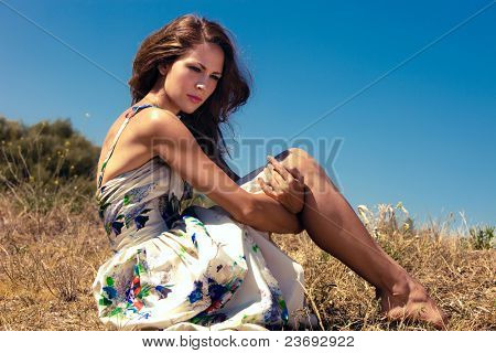 young woman in summer dress sits barefoot in grass, sunny summer day