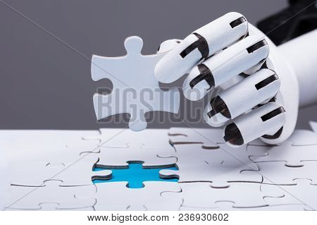 Close-up Of A Robotic Hand Solving Jigsaw Puzzle