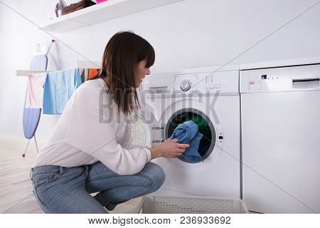 Young Woman Putting Dirty Cloth Into Washing Machine At Laundry Room