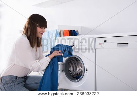 Young Woman Smelling Blue Cloth After Washing In Washing Machine