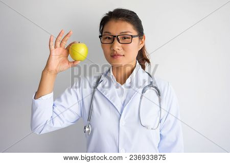 Content Young Asian Female Doctor Showing Apple. Healthy Nutrition Concept. Isolated Front Closeup V