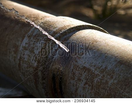 An Irrigation Pipe That Is So Old And Rusted That It Has Sprung A Gushing Leak.