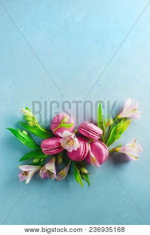 French Macaroons Vignette On A Concrete Background With Spring Alstroemeria Flowers. Dessert Photogr