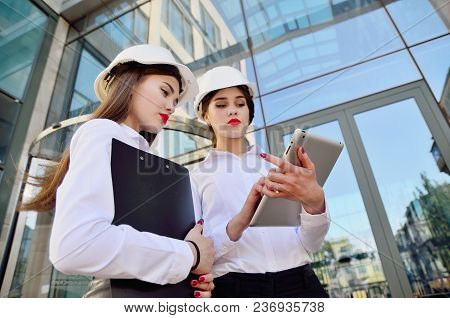 Girls In Building White Helmets With Tablets In Hands On The Background Of A Glass Office Building.