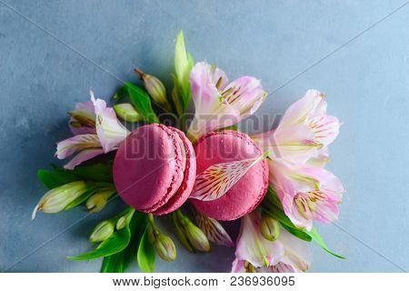 Pink Macaroon Close-up With Spring Flowers And Buds. French Dessert On A Blue Stone Background With