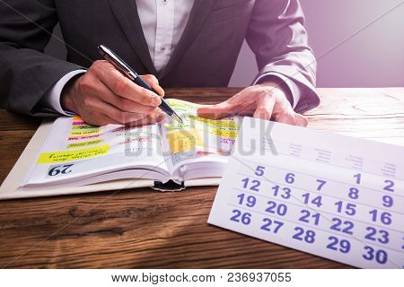 Businessperson's Hand Checking Schedule In Diary