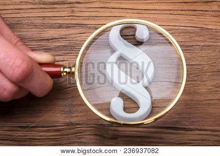 Businessperson Holding Magnifying Glass Over Paragraph Symbol