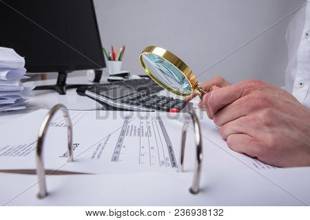 Businessperson Examining Invoice Through Magnifying Glass