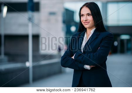 Portrait of smiling businesswoman in suit, business center on background. Modern financial building, cityscape. Successful female businessperson
