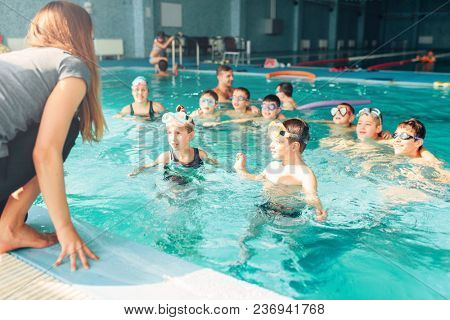 Female instructor teaches children how to swim. Kids with goggles in water listening trainer. Happy kids in modern sport center. Concept of fun, leisure and recreation.