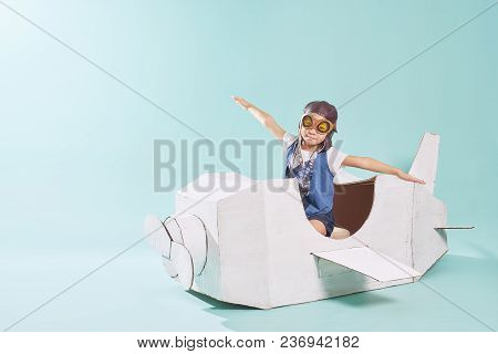Little Cute Girl Playing With A Cardboard Airplane. White Retro Style Cardboard Airplane On Mint Gre