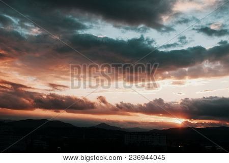 Dramatic Cloudy Sunset With Yellow And Blue Based Colors Abouve Mountains