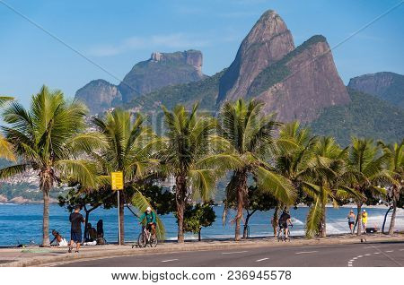 Row Of Palm Trees In Ipanema Beach, Two Brothers And Gavea Mountains In The Horizon, Rio De Janeiro,