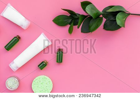 Natural Cosmetics For Skin Care Near Green Leaves On Pink Background Top View.