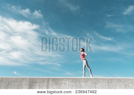 Active Young Girl Warm-up In The Open Air Before Training, Gaining Strength