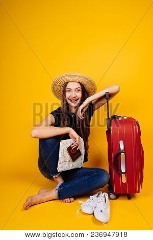 Happy Long-haired Girl In A Straw Hat Goes On Holiday, With A Large Red Suitcase, Holds Tickets For