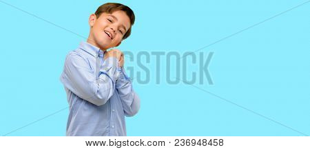 Handsome toddler child with green eyes confident and happy with a big natural smile laughing over blue background