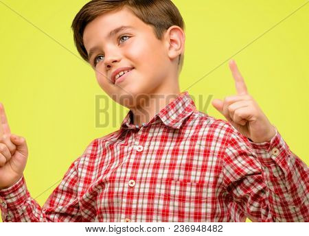 Handsome toddler child with green eyes happy and surprised cheering pointing up over yellow background