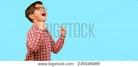Handsome toddler child with green eyes happy and excited expressing winning gesture. Successful and celebrating victory, triumphant over blue background