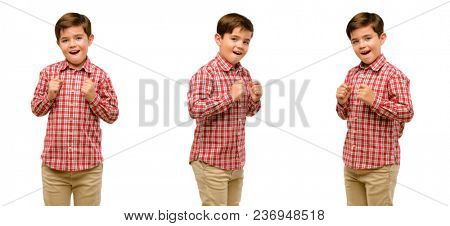Handsome toddler child with green eyes happy and surprised cheering expressing wow gesture