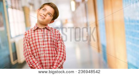 Handsome toddler child with green eyes confident and happy with a big natural smile laughing looking up at school corridor