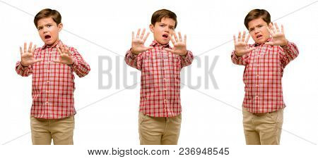 Handsome toddler child with green eyes disgusted and angry, keeping hands in stop gesture, as a defense, shouting