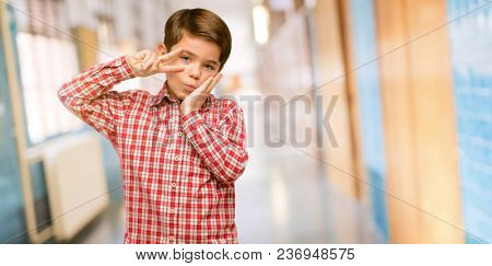Handsome toddler child with green eyes looking at camera through fingers in victory gesture winking the eye and blowing a kiss at school corridor
