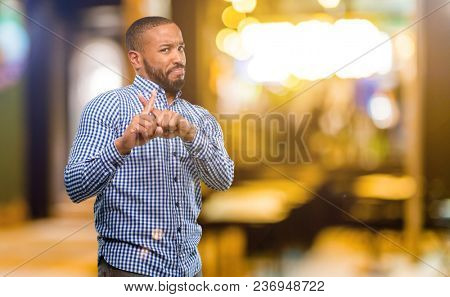 African american man with beard annoyed with bad attitude making stop sign with hand, saying no, expressing security, defense or restriction, maybe pushing at night